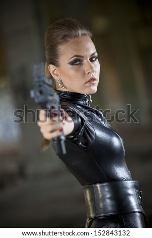 woman in leather catsuit aiming with a gun in the camera - stock photo