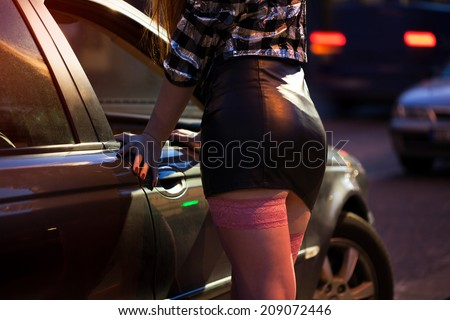 Woman in leather mini skirt standing next to car - stock photo