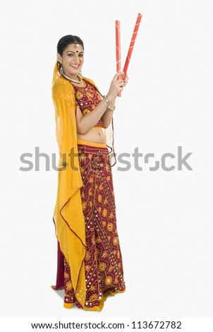 Woman in lehenga choli holding dandiya sticks - stock photo