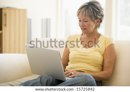 Woman in living room with laptop smiling - stock photo