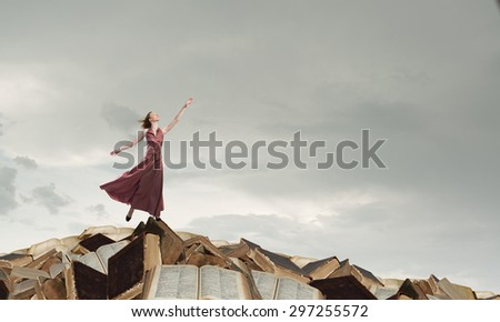 Woman in long dress standing on pile of old books - stock photo
