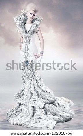 woman in long white dress with feather collar on sand - stock photo