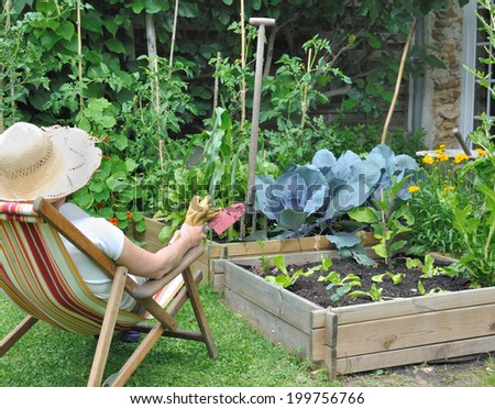woman in lounge chair contemplating her garden with tools in hand - stock photo