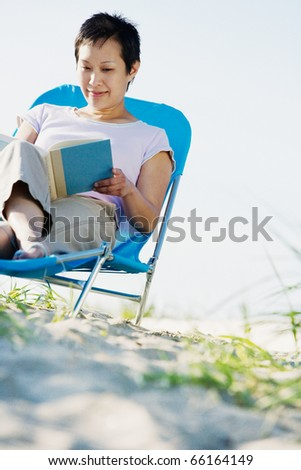 Woman in lounge chair reading book - stock photo