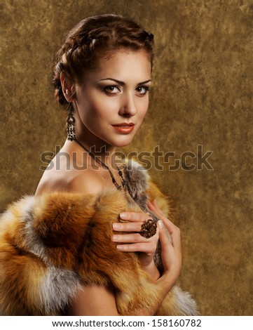 Woman in luxury fur coat. Vintage style. Golden background. - stock photo