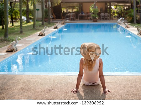 woman in luxury spa resort near the swimming pool - stock photo