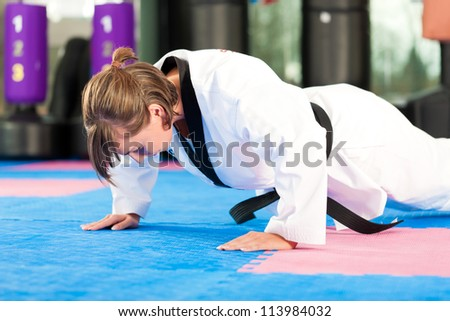 Woman in martial art training in a gym, she is stretching and warming up - stock photo