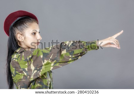 Woman in military clothes pointing to the right. - stock photo