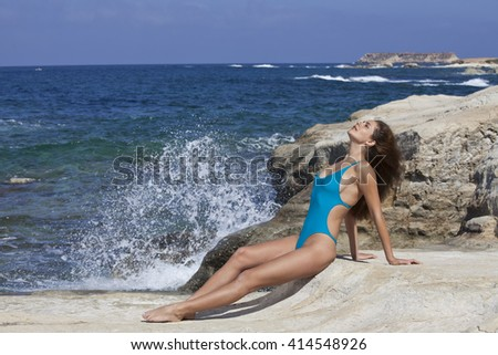Woman in modish swimsuit sunbathing at the rocky beach