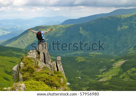 Woman in montains  on rock with back pack with his arms splayed and say: I love this world