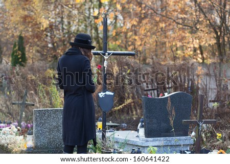 Woman in mourning clothes standing above headstone - stock photo