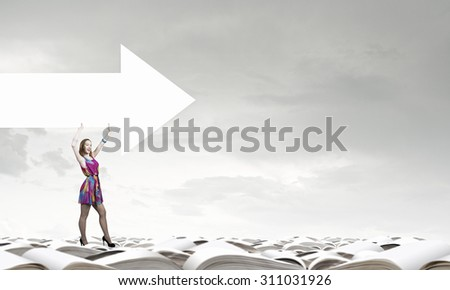 Woman in multicolored dress with arrow banner in hands