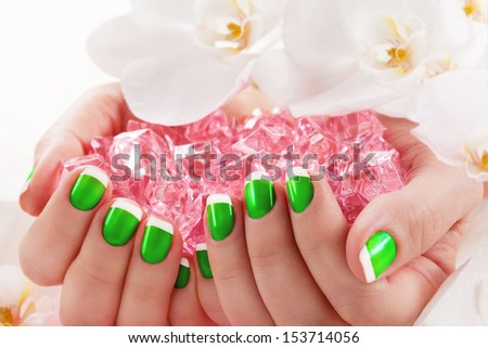 Woman in nail salon receiving manicure by beautician - stock photo
