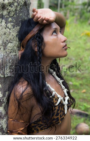 woman in native costume stands leaning against a tree in the woods - stock photo