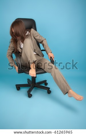 Woman in office chair trying not to fall - stock photo
