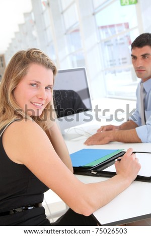 Woman in office signing contract