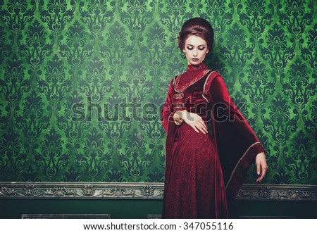 Woman in old styled clothes on green vintage pattern background. Rich history. Vintage and retro toning. Rococo style - stock photo