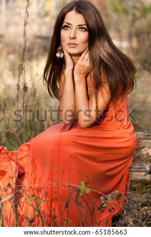 woman in orange dress at the nature - stock photo