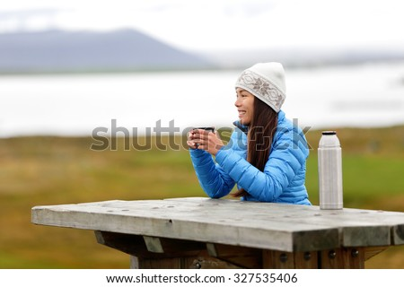 Woman in outdoors drinking coffee from thermos bottle flask sitting outside wearing warm down jacket and knit hat. Active young mixed race Asian Chinese Caucasian woman enjoying traveling on Iceland. - stock photo