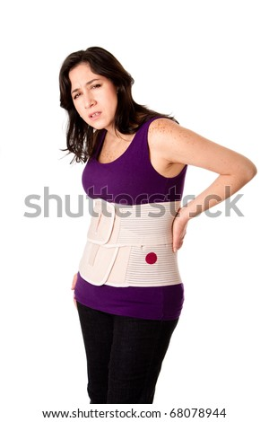 Woman in pain from back injury wearing an orthopedic body brace corset, isolated. - stock photo