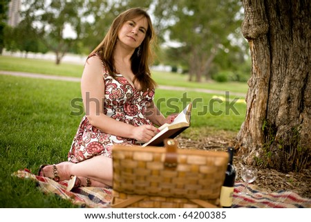 Woman in park with picnic basket and book - stock photo