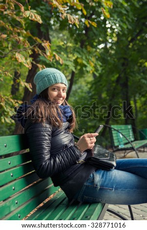 woman in park writes sms