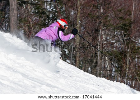 Woman in pink jacket skiing down a hill.