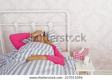 Woman in pink pajama with headache and tissues lying in bed with washcloth - stock photo