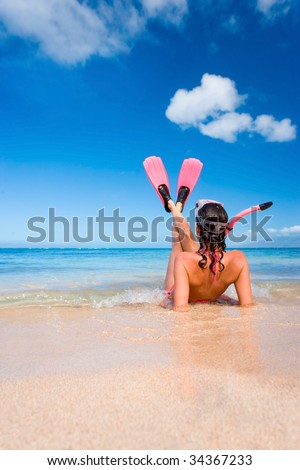 woman in pink snorkel gear on sandy beach - stock photo