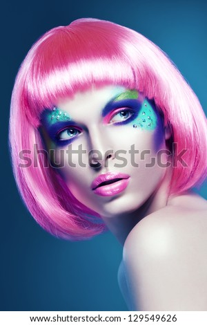 woman in pink wig on blue background - stock photo