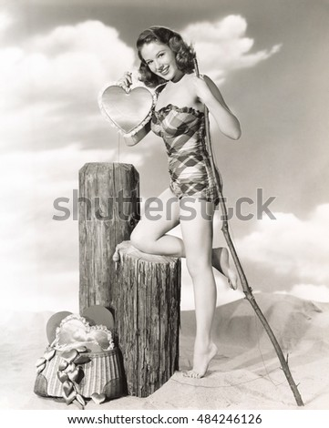 Woman in plaid bathing suit holding satin heart