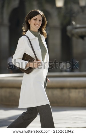 Woman in polo neck jumper and white coat walking in plaza, carrying handbag, smiling, portrait