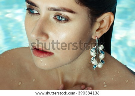Woman in Pool Sapphire and Pearls Earrings - stock photo