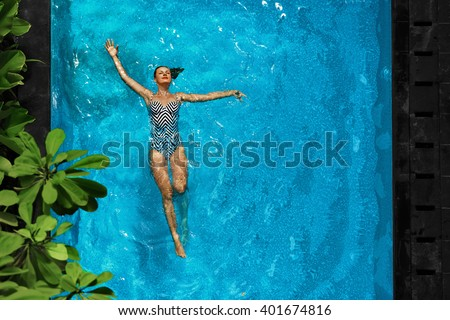 Woman In Pool Water. Beautiful Happy Girl With Sexy Fit Body Relaxing, Floating In Swimming Pool At Spa Hotel. Summer Holidays Vacation. Healthy Lifestyle. Wellness, Beauty, Health Concept. Recreation - stock photo
