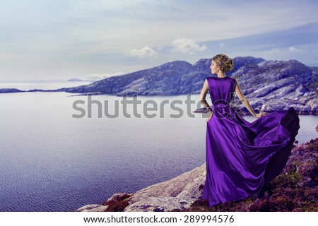 Woman in Purple Dress Looking to Mountains Sea, Waving Gown Flying on Wind, Elegant Girl Waiting on Coast - stock photo