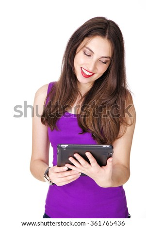 Woman in purple tank top happy smiling and holding a tablet in her hands. Fit and athletic Caucasian brunette girl posing on white background. - stock photo
