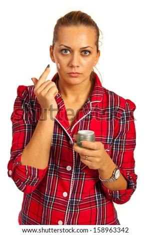 Woman in pyjamas applying lotion before bed isolated on white background - stock photo
