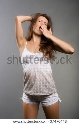 woman in pyjamas yawning against grey background - stock photo