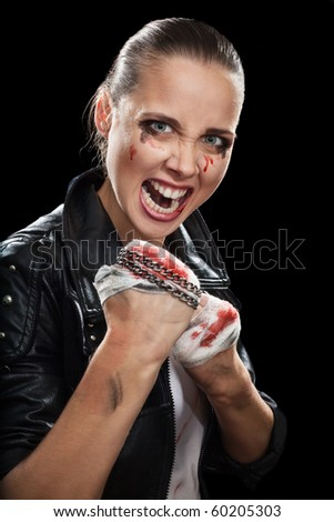 Woman in rage fighting on street with blood on fists and black background - stock photo