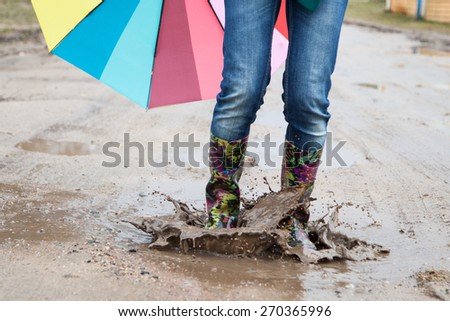Woman in rain boots jumps into a puddle - stock photo