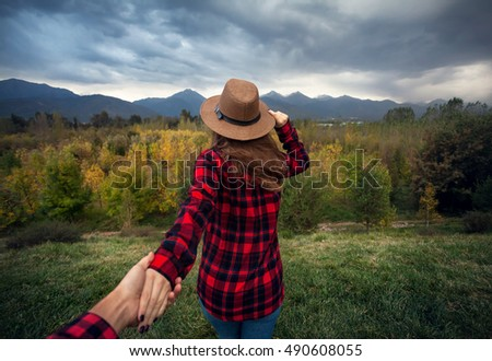 Woman in red checked shirt and hat holding man by hand going to Autumn forest with mountains and cloudy sky