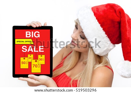 woman in red Christmas hat holding tablet pc computer  with big sale on screen