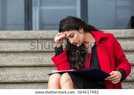 woman in red coat  sitting in stairs reading looking down