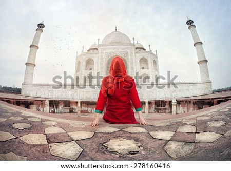 Woman in red costume sitting on the floor and looking at Taj Mahal in Agra, Uttar Pradesh, India - stock photo