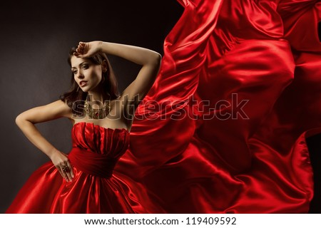 Woman in red dress dancing with flying fabric, Fashion Model Girl Posing with waving cloth