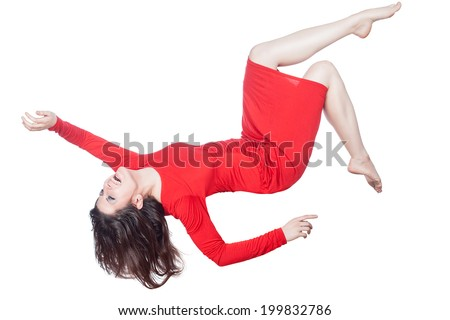 Woman in red dress floating in the air falling on a white background. - stock photo