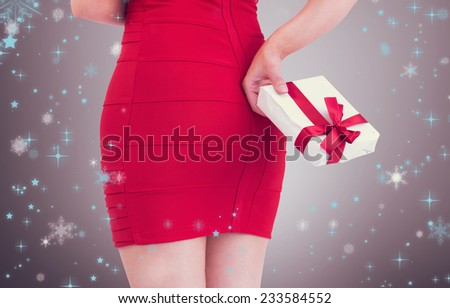 Woman in red dress holding gift against grey vignette - stock photo