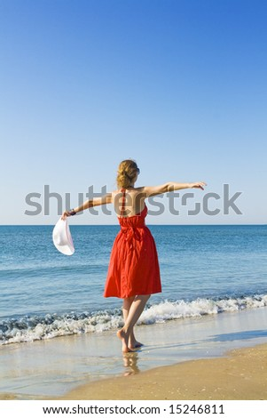 woman in red dress  holding white hat dancing on the beach - stock photo