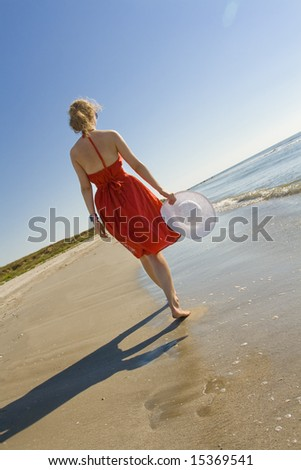 woman in red dress holding white hat walking on the beach - stock photo