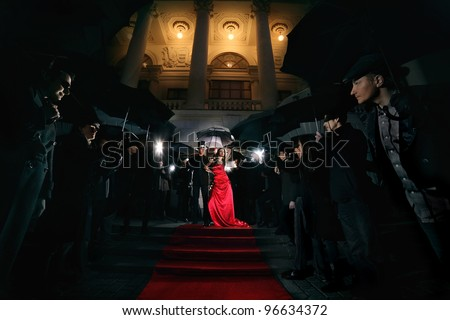 woman in red dress posing in front of paparazzi - stock photo